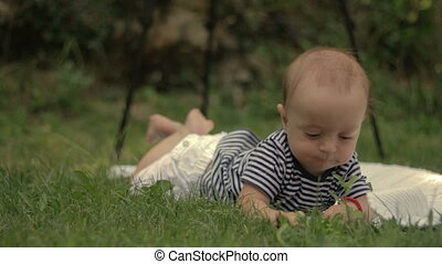 A small child lies on the grass grins and plays close-up