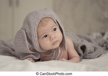 A small child of 1 months in a gray hat with ears looks to the side. Soft light soft focus