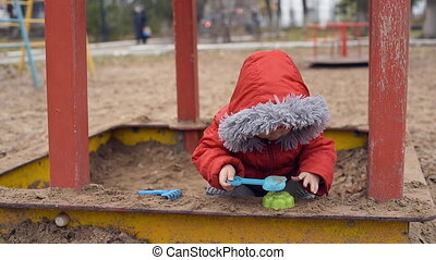 a small child playing in a sandbox - a small child plays in...