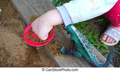 A small child playing in a sandbox with a dinosaur