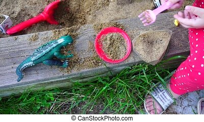 A small child playing in a sandbox with a dinosaur.