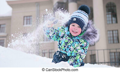A small child plays on a snowy mountain, throws snow and laughs . Sunny frosty day. Fun and games in the fresh air.