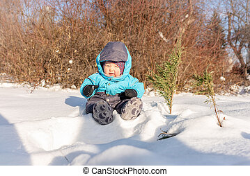 A small child sits in the snow at park