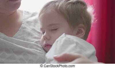 A small child sleeping on hands at mum. The tenderness and care of children.