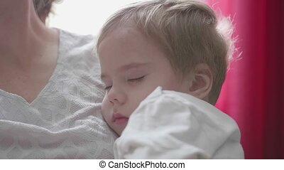 A small child sleeping on hands at mum. The tenderness and...