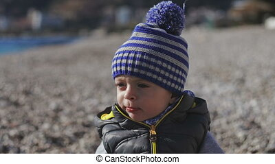 A small child smiles into the camera and plays on the beach with pebbles.