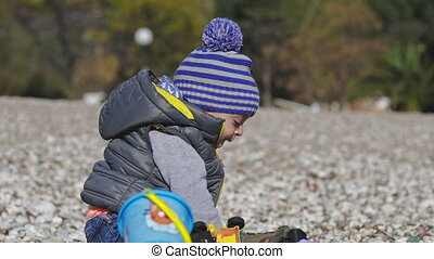 A small child smiles into the camera and plays on the beach with toys.
