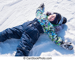 A small child walks in the winter Park. Playing and smiling baby on white fluffy snow. Active rest and games.