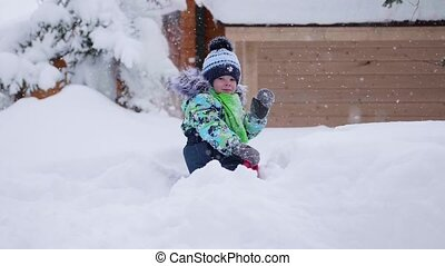 A small child walks in the winter Park. Playing and smiling...