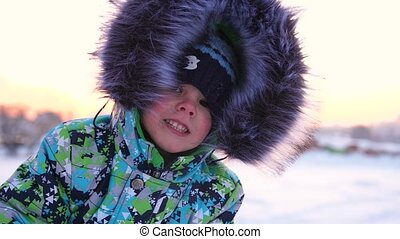 A small child walks in the winter Park. Playing and smiling baby on white fluffy snow. Face close-up. Active rest and games.