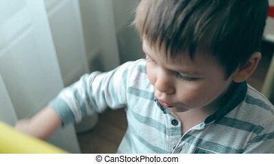 A small child wipes chalk with his finger on the Board