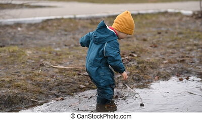 a small child with a stick in his hand playing in a puddle...