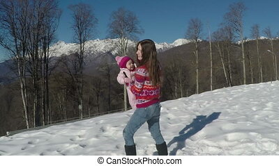 a small child with his mother playing in the snow in the mountains. slow motion