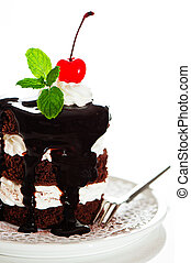 A small chocolate cake with 2 layer white cream, cherry and mint on top on a white background as a studio shot