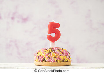 coloruful cupcake with number five shaped candle for birthday