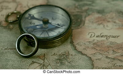 A small compass and a ring on top of a map