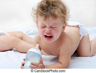 a small curly boy is standing on all fours, holding a bottle of milk and crying heavily