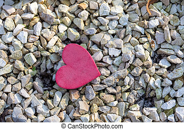 a small decorative red heart on stones in nature - a single ...