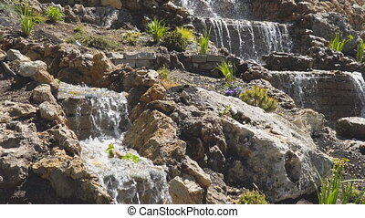 A small decorative waterfall in the Park or in the garden