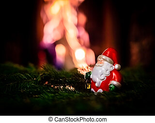 A small figurine of Santa Claus stands on green spruce branches against the background of flames in the fireplace.