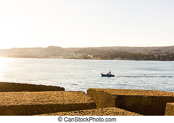 A small fishing boat leaving the port in Denia, Spain