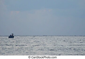 A small fishing boat on a silver sea.
