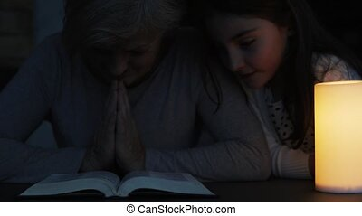 A small girl and grandmother praying at home.