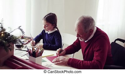 A small girl and her grandfather in a wheelchair writing Christmas cards together.