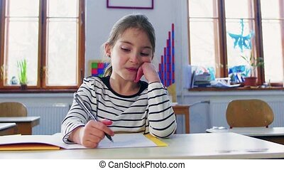 A small girl at the desk at school, writing. - A small girl...