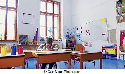 A small girl at the desk at school, writing. - An small girl...