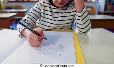A small girl at the desk at school, writing. - An...