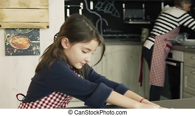 A small girl cooking with grandmother at home. - A small...