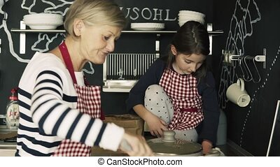 A small girl cooking with grandmother at home.