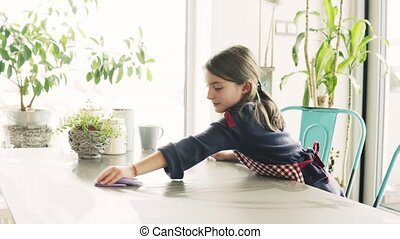 A small girl doing housework at home. - A small girl wiping...