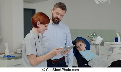 A small girl, father and dentist in surgery, dental checkup...