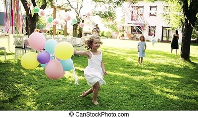 A small girl on birthday party outdoors in garden in summer...