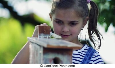 A small girl outside, painting a wooden birdhouse. - A small...