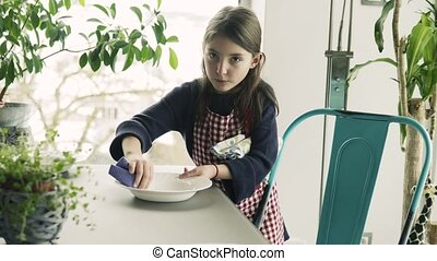 A small girl setting the table at home. - A small girl...
