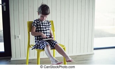A small girl sitting on chair indoors at home, playing with smartphone.