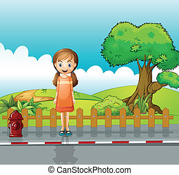 A small girl standing near the wooden fence