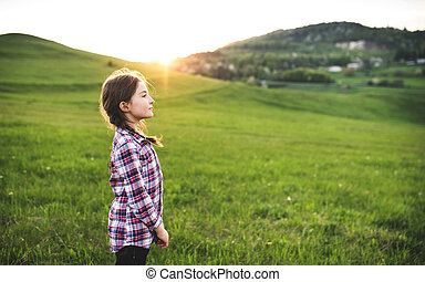 A small girl standing outside in nature.