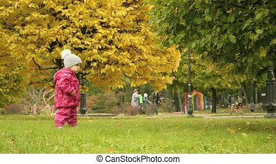 a small girl walking in the park