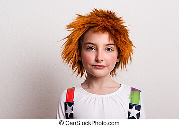 A small girl with a wig and a clown costume in a studio.