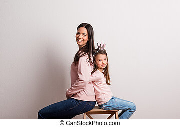 A small girl with crown headband and her mother sitting back to back in a studio.