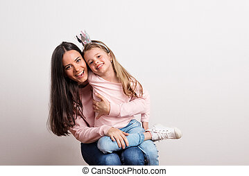 A small girl with crown headband and her mother sitting in a studio.