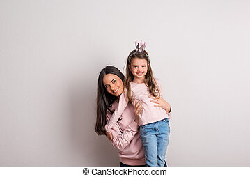 A small girl with crown headband and her mother standing in a studio.