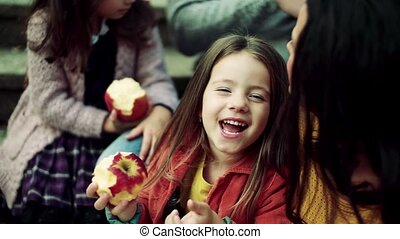 A small girl with family having picnic in autumn nature,...