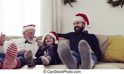 A small girl with father and grandfather sitting on a sofa at Christmas time, having fun.
