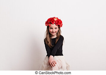 A small girl with flower headband sitting in a studio, hands on her knees.