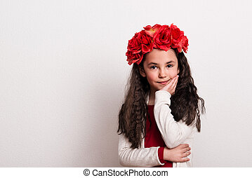 A small girl with flower headband standing in a studio, chin resting on her hand.